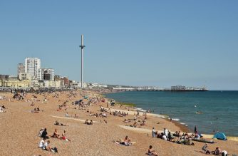 People sunbathe on the beach looking east towards the i360 in Hove, on the south coast of England on May 31, 2020 on the eve of a further relaxation of the novel coronavirus lockdown rules. - The UK government has set out a gradual easing of lockdown measures in England, with socially distanced groups of six friends and families allowed to meet in parks and gardens from June 1. (Photo by Glyn KIRK / AFP)