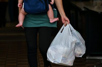 This photo taken on June 24, 2020 shows a customer carrying her shopping in plastic bags at a supermarket in Tokyo. - Retailers in Japan began charging for plastic bags on July 1, a move aimed at curbing Japanese consumers' love for packaging and finally bringing the country in line with other major economies. (Photo by CHARLY TRIBALLEAU / AFP)