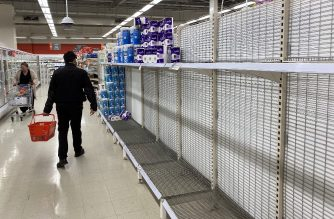 A shopper walks past near-empty shelves of toilet paper at a supermarket in a Melbourne on June 26, 2020. - Supermarkets imposed purchase limits on toilet paper across Australia on June 26 following panic buying by people rattled over a surge in coronavirus cases in the country's second-biggest city. (Photo by William WEST / AFP)