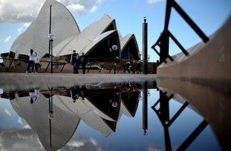 People walking around the Australia's iconic landmark Opera House are reflected in a puddle in Sydney on June 30, 2020. (Photo by Saeed KHAN / AFP)