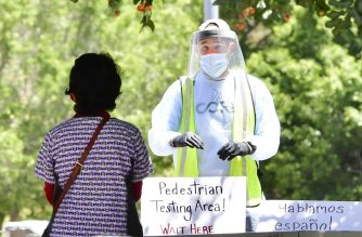 A volunteer dressed in full protective gear gives directions to a woman at a walk-in COVID-19 test site on June 30, 2020 in Los Angeles, California. - The US will start combining test samples to be tested in batches, instead of one by one, hoping to dramatically boost screening for the coronavirus, as California passes the threshold of 6,000 coronavirus-related deaths three months after statewide Stay-At-Home orders went into effect to try and stem the virus. (Photo by Frederic J. BROWN / AFP)