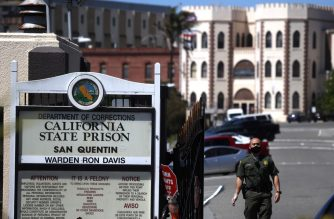 (FILES) In this file photo taken on June 29, 2020 a California Department of Corrections and Rehabilitation (CDCR) officer wears a protective mask as he stands guard at the front gate of San Quentin State Prison in San Quentin, California. - The number of COVID-19 cases has exploded in one of California's oldest prisons, San Quentin, as more than 1,000 inmates have tested positive for the virus, authorities in the US state announced Tuesday. (Photo by JUSTIN SULLIVAN / GETTY IMAGES NORTH AMERICA / AFP)