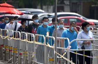 People wearing face masks queue to take swab tests during a mass testing for COVID-19 in Beijing on July 1, 2020. (Photo by Noel Celis / AFP)