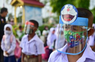 Students wearing face shields observe social distancing as they line up to attend classes in a school in the southern Thai province of Narathiwat on July 1, 2020, as schools reopened after being temporarily closed due to the threat of the COVID-19 novel coronavirus. - Mask-wearing pupils returned to the courtyard of their schools on July 1, as Thailand pushed towards some sense of normality with the coronavirus largely in check. (Photo by Madaree TOHLALA / AFP)