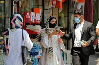Iranian pedestrians wearing protective masks due to the COVID-19 pandemic, walk along a street in the capital Tehran on July 1, 2020. (Photo by ATTA KENARE / AFP)