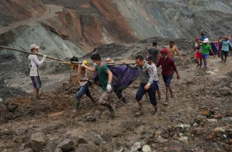 Rescuers recover bodies near the landslide area in the jade mining site in Hpakhant in Kachin state on July 2, 2020. - The battered bodies of more than 120 jade miners were pulled from a sea of mud after a landslide in northern Myanmar on July 2 after one of the worst-ever accidents to hit the treacherous industry. (Photo by Zaw Moe Htet / AFP)