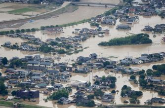 This picture shows inundated houses due to heavy rain in Hitoyoshi, Kumamoto prefecture on July 4, 2020. - Fourteen people were feared dead at a nursing home in western Japan on July 4 as record rainfall triggered massive floods and landslides, forcing authorities to issue evacuation advisories for more than 200,000 residents. (Photo by STR / JIJI PRESS / AFP) / Japan OUT