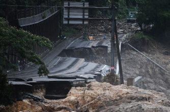 """A collapsed road caused by heavy rain is seen in Kuma, Kumamoto prefecture on July 7, 2020. - Emergency services in western Japan were """"racing against time"""" to rescue people stranded by devastating floods and landslides, with at least 50 feared dead and more torrential rain forecast. (Photo by CHARLY TRIBALLEAU / AFP)"""