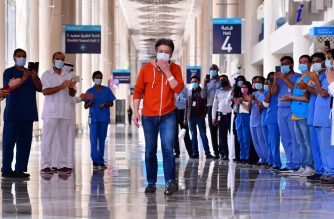 Hiroaki Fujita from Japan, the last patient at the temporary COVID-19 hospital built in downtown Dubai in the United Arabic Emirates, is acclaimed by nurses and doctors as he leaves the facility, on July 7, 2020. (Photo by GIUSEPPE CACACE / AFP)