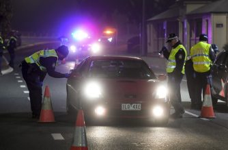 Police in the southern New South Wales (NSW) border city of Albury check cars crossing the state border from Victoria on July 7, 2020 as authorities close the border due to an outbreak of COVID-19 coronavirus in Victoria. - Australia on July 7 ordered millions of people locked down in its second-biggest city to combat a surge in coronavirus cases, as nations across the planet scrambled to stop the rampaging pandemic. (Photo by William WEST / AFP)