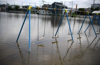"""Employees clear flood waters from a store in Kurume, in Fukuoka Prefecture on July 8, 2020. - Japan will deploy more troops to search for survivors of devastating floods and landslides that have killed at least 52 people in the southwest of the country, Prime Minister Shinzo Abe pledged (Photo by CHARLY TRIBALLEAU / AFP) / """"The erroneous mention[s] appearing in the metadata of this photo by CHARLY TRIBALLEAU has been modified in AFP systems in the following manner: [Fukuoka] instead of [Kumamoto]. Please immediately remove the erroneous mention[s] from all your online services and delete it (them) from your servers. If you have been authorized by AFP to distribute it (them) to third parties, please ensure that the same actions are carried out by them. Failure to promptly comply with these instructions will entail liability on your part for any continued or post notification usage. Therefore we thank you very much for all your attention and prompt action. We are sorry for the inconvenience this notification may cause and remain at your disposal for any further information you may require."""""""