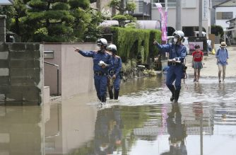 Fire brigade officers check on residents following heavy rain in Omuta, Fukuoka Prefecture on July 8, 2020. - Torrential rain pounded central Japan on July 8 as authorities said 58 people were feared dead in days of heavy downpours that have triggered devastating landslides and terrifying floods. (Photo by STR / JIJI PRESS / AFP) / Japan OUT