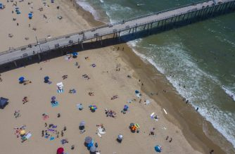 An aerial view shows people on the beach and in the water during a heatwave as coronavirus cases reach new record levels in states across the nation, in Hermosa Beach, California, on July 12, 2020. - Los Angeles County beaches are reopened after they were re-closed over the Fourth of July weekend because of fears that large gatherings would further accelerate the spread of COVIC-19. More than 2,000 people are currently hospitalized with COVID-19 in Los Angeles County. (Photo by DAVID MCNEW / AFP)
