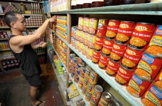(FILE) A customer searches the shelves for canned goods at a market in Manila on April 13, 2008. / AFP PHOTO / JAY DIRECTO