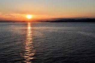 燃えるような赤金色の太陽が現れ、山上から船に向かって波の上にキラキラ輝く道ができる。