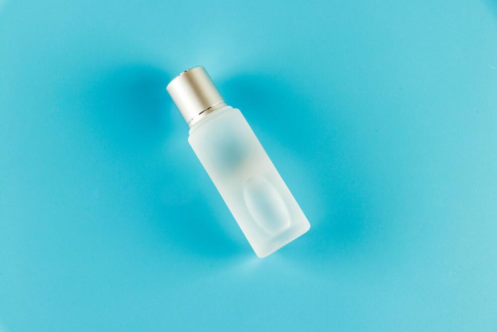 水色の背景にある化粧水の瓶