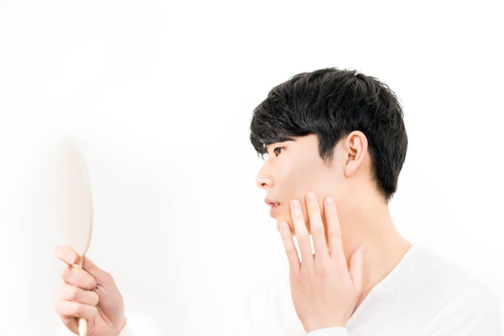 鏡を見ながら頬に手を当てる男性