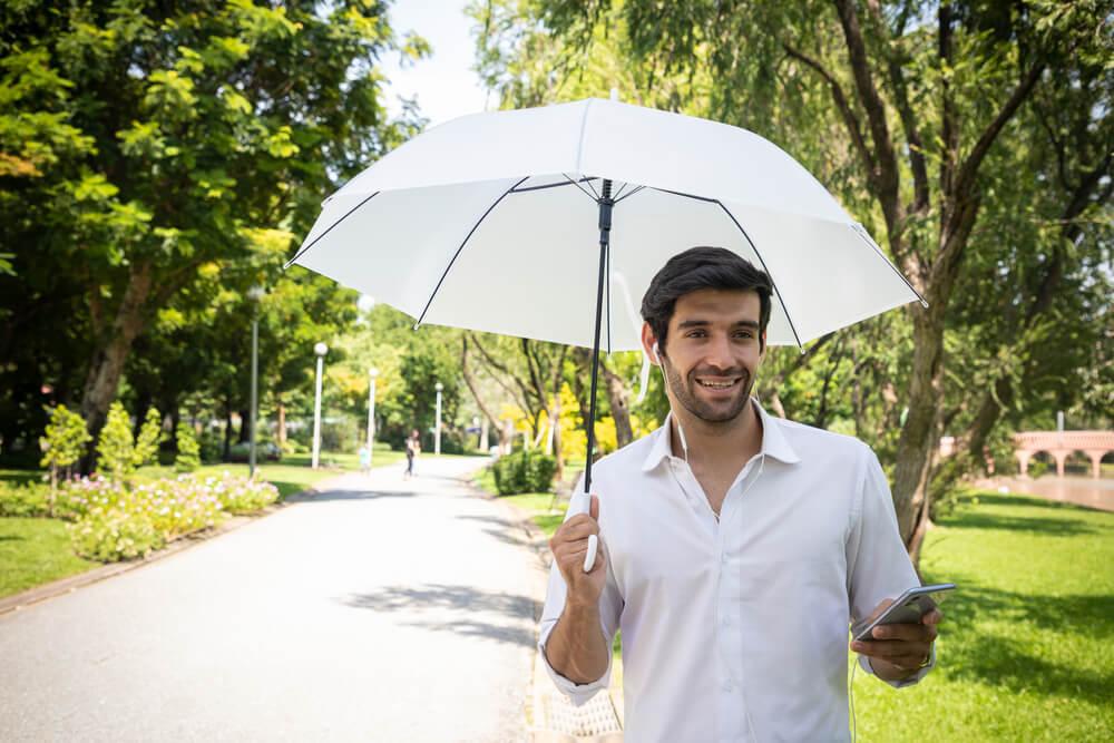 白の日傘をさす男性