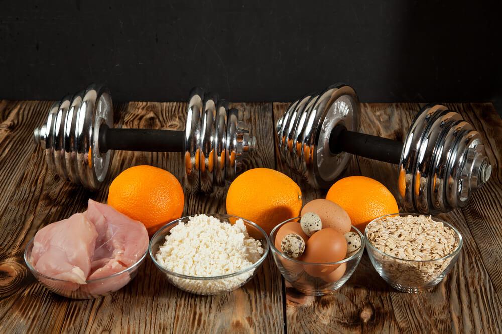 テーブル上のダンベルと穀類・卵などの食材