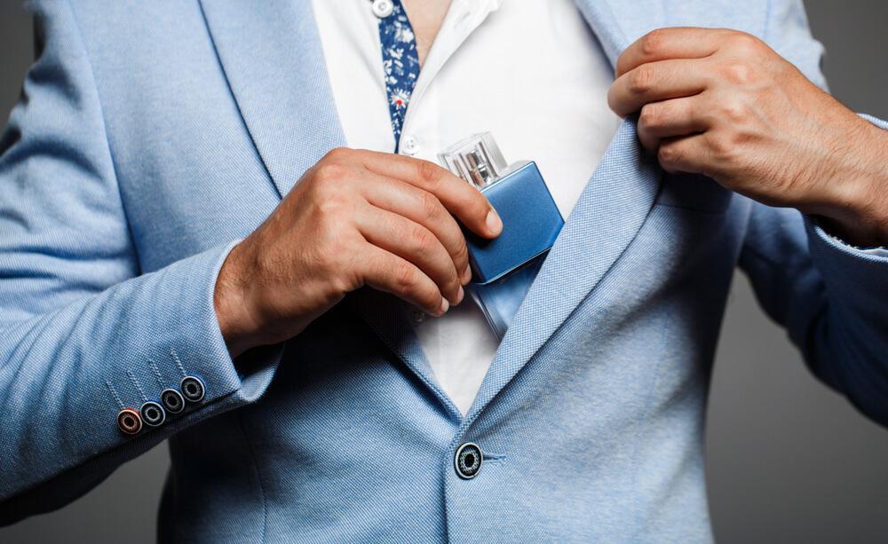 スーツから香水を出す男性