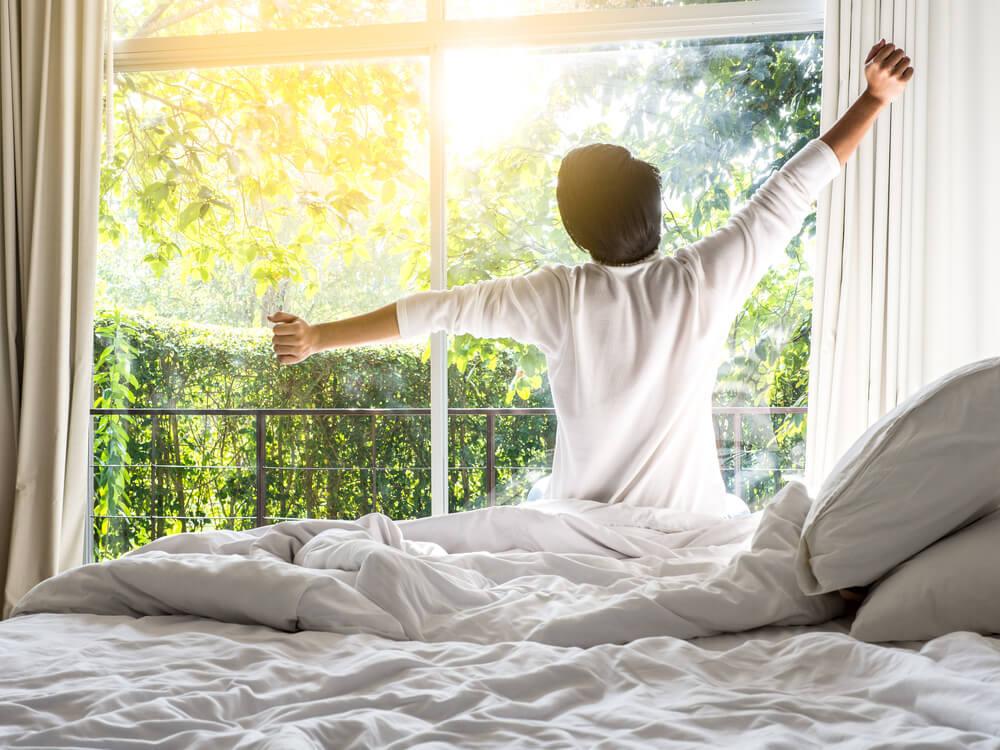 起床後に朝日を浴びる男性