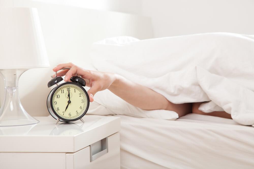 目覚まし時計を止める男性
