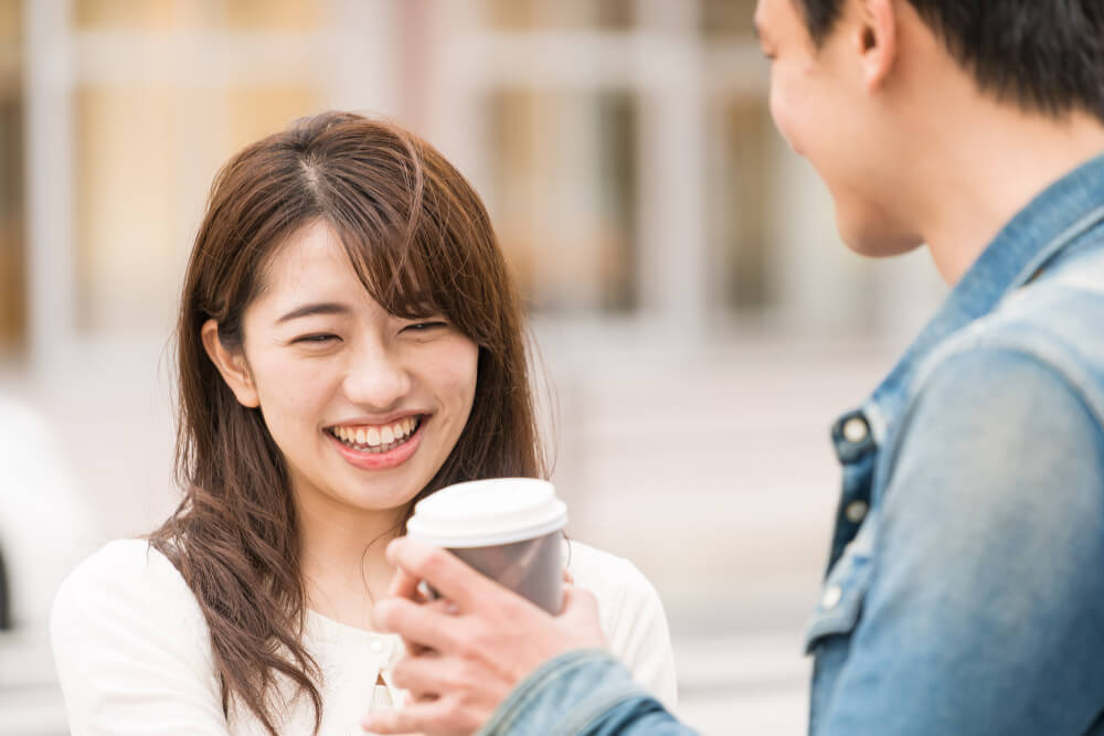 飲み物を受け取り笑顔になる女性