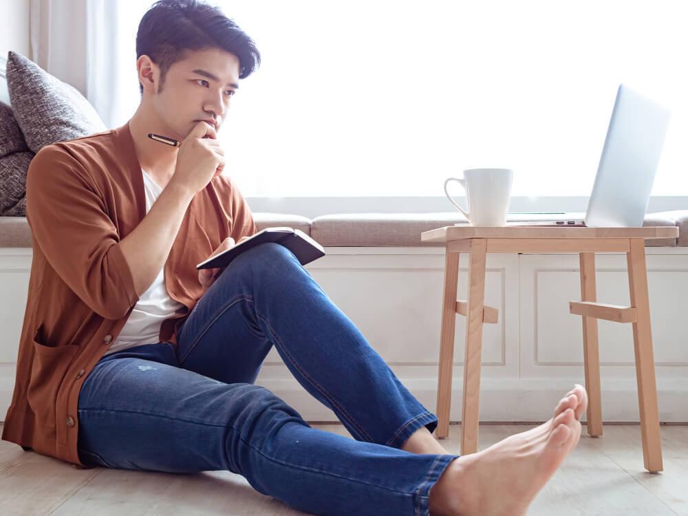 手帳を膝に乗せ考える男性