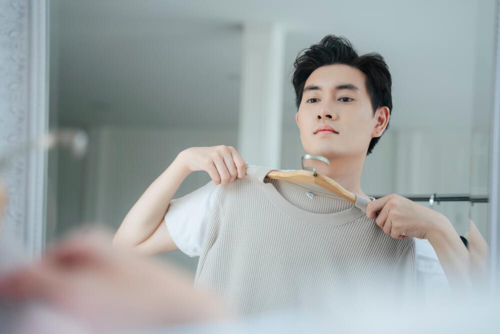 鏡を見ながら服を選ぶ男性