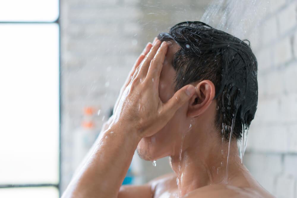 シャワーを頭から浴びる男性