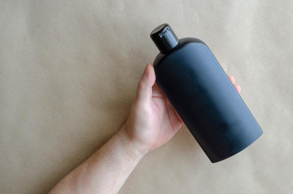 ボディソープのボトルを持つ人
