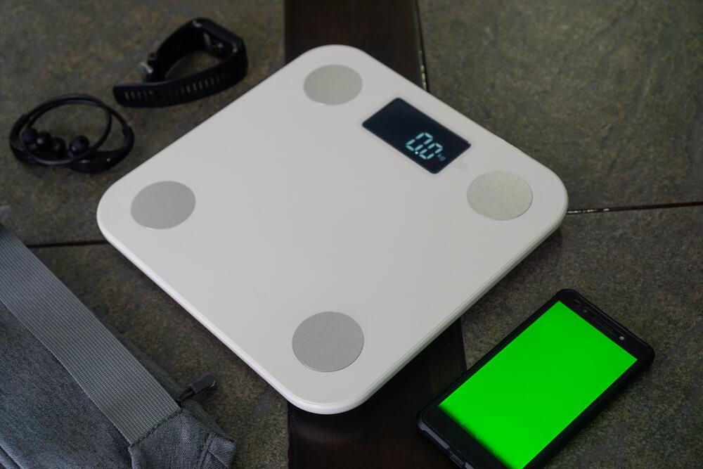 体重計とスマートフォン、イヤホン