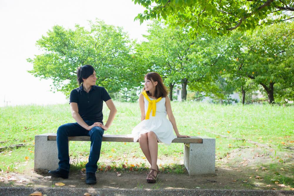 公園のベンチに座って話をする男女