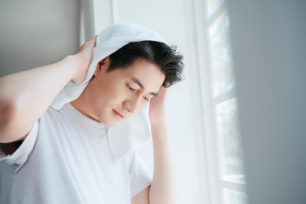髪をタオルで拭く男性