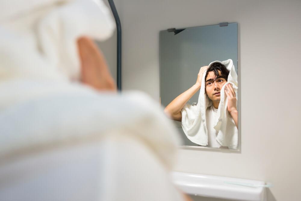 鏡の前で髪を拭く男性