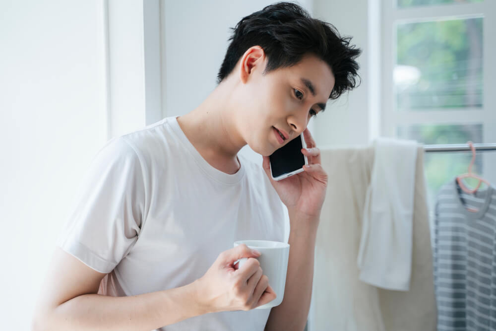コーヒーを飲みながら携帯で話す男性