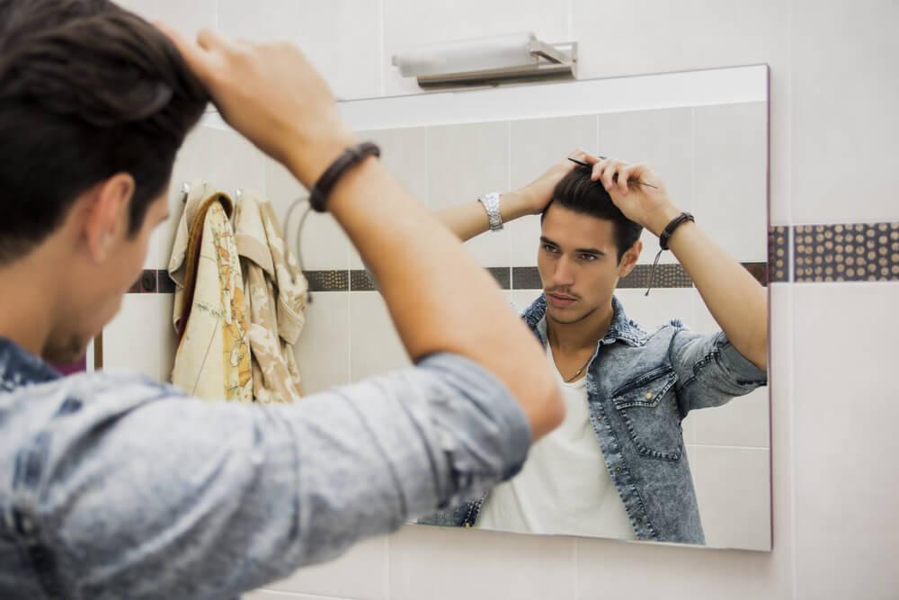 鏡の前で髪に櫛を通す男性
