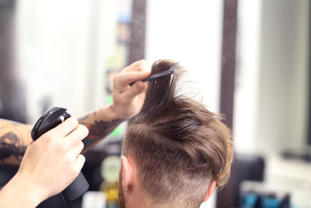 ヘアスプレーをかける美容師