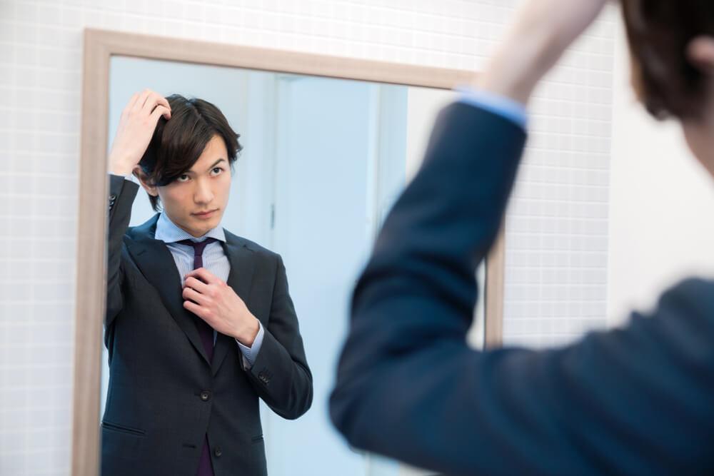 鏡の前で髪型をセットする男性