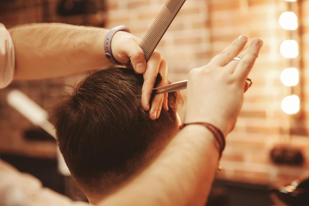 美容室で髪をカットする男性