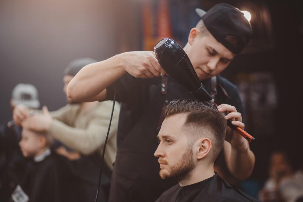 髪にドライヤーをあてる美容師
