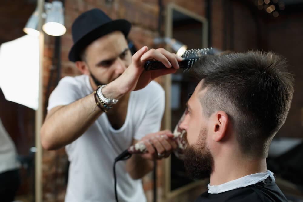 前髪を立ち上げる美容師