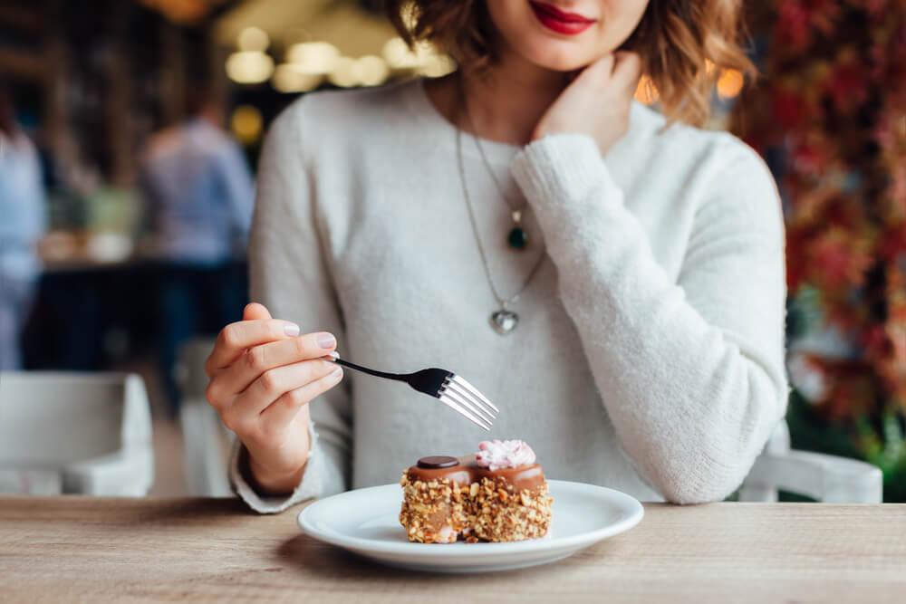 カフェでケーキを食べようとする女性