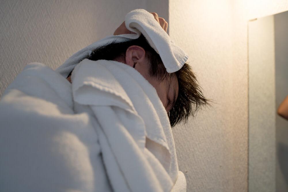 洗面所で髪をタオルドライする男性
