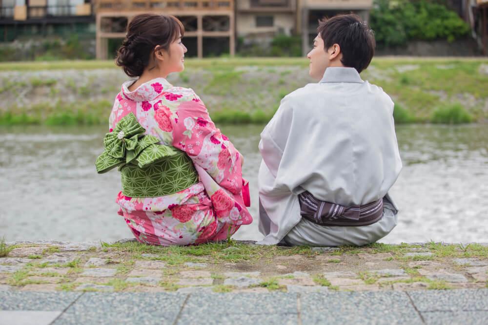 川辺で浴衣姿で談笑するカップル