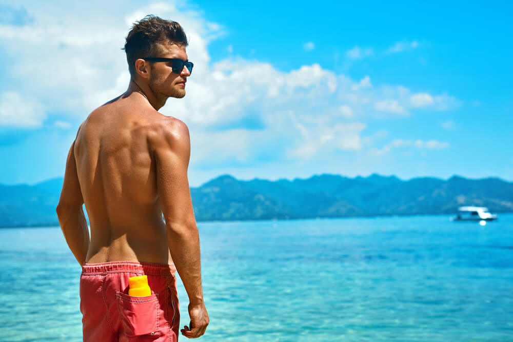ビーチに佇む水着姿の男性