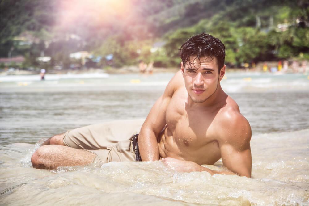 浜辺に横たわる筋肉質の男性