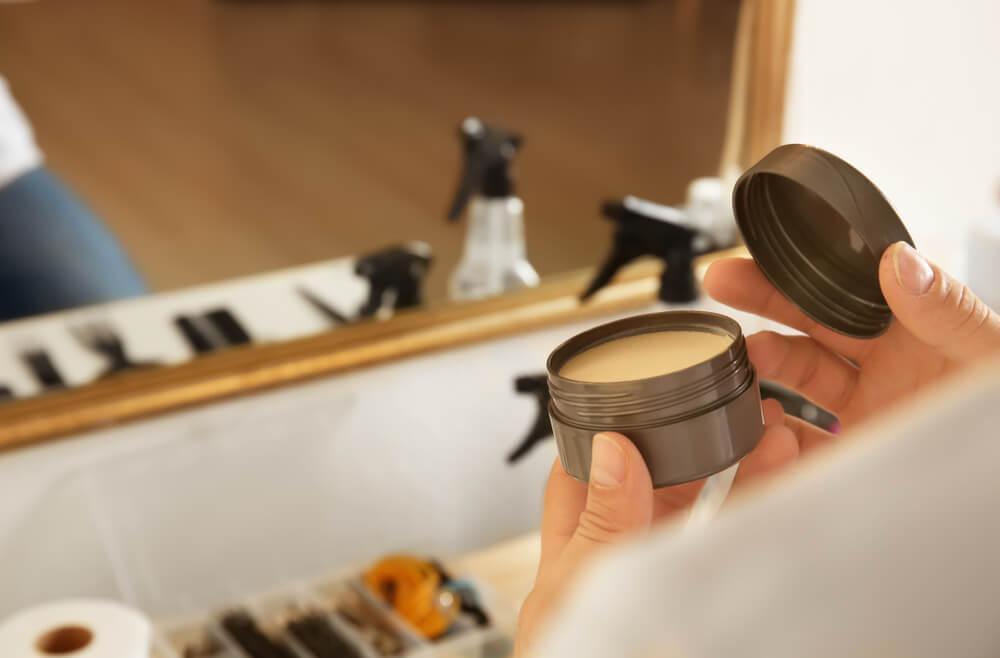 鏡の前でヘアワックスを持つ人