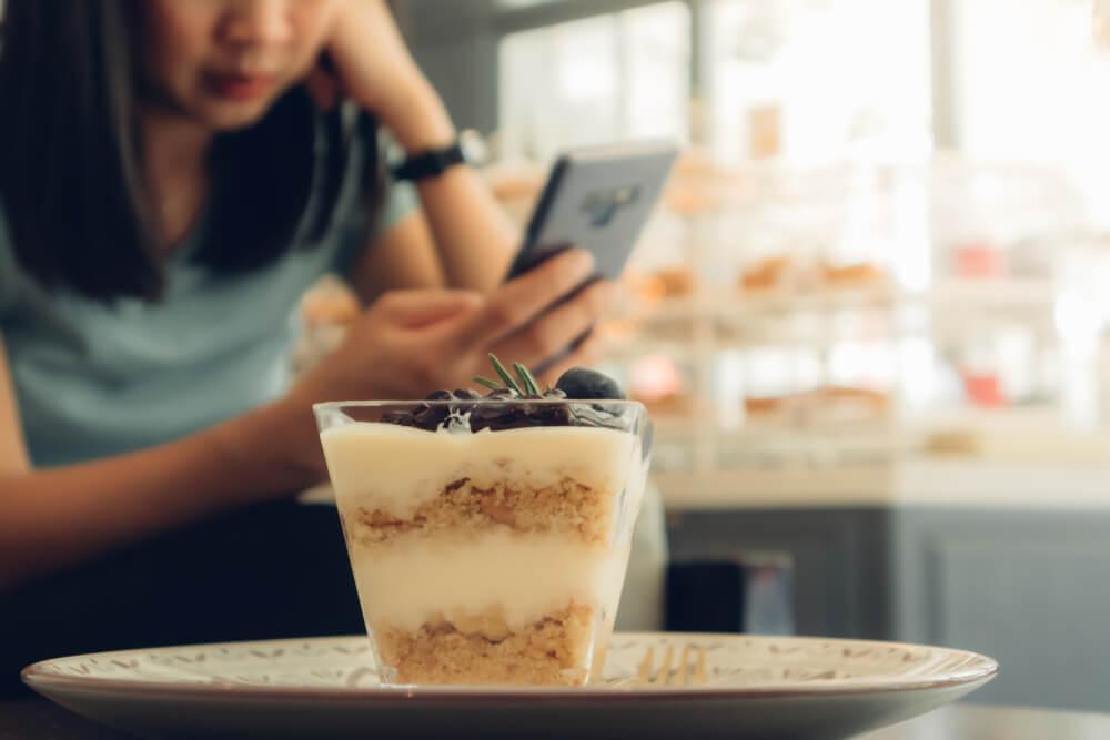 カフェでスマートフォンを見る女性