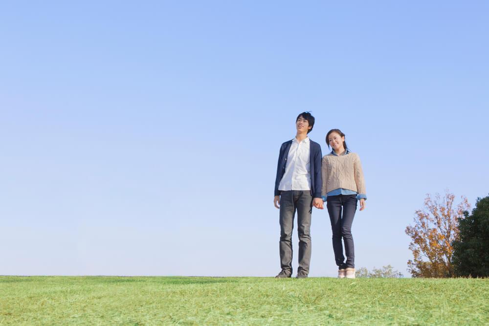 野原で手をつないで歩くカップル
